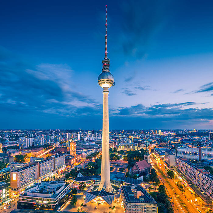 Berliner Fernsehturm mit beleuchteter Innenstadt bei Nacht