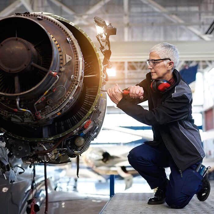Mechanikerin führt Wartungsarbeiten an einem Jet-Triebwerk durch