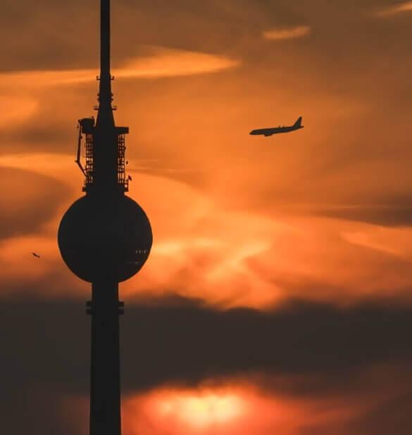 Berliner Fernsehturm bei Dämmerung mit Flugzeug im Hintergrund