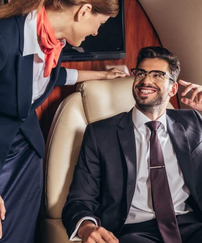 Flugbegleiterin und Fluggast sprechen im Privatjet