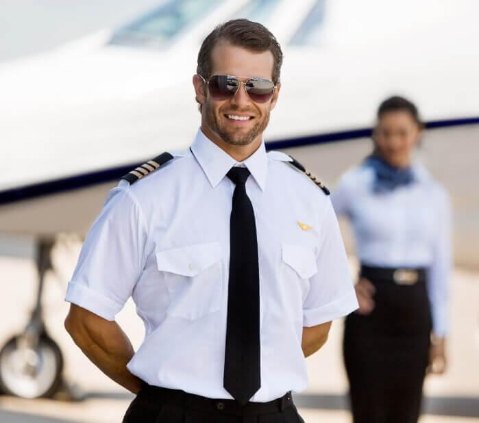 Flugkapitän und Flugbegleiterin stehen vor einem Privatjet