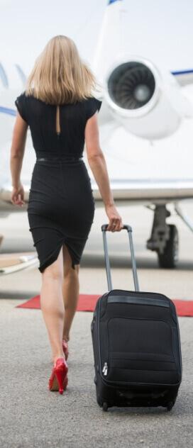 Frau mit Reisekoffer geht zum Privatjet