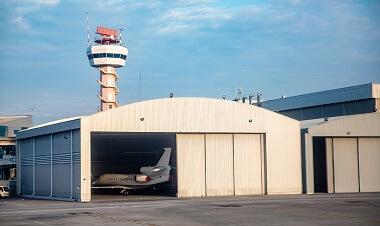 Privatjet steht im Hangar mit Tower im Hintergrund